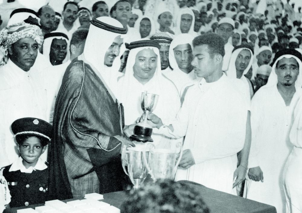 الأمير عبدالله الفيصل يسلم كأس إحدى مباريات المدارس ويظهر فتيحي بجانبه.