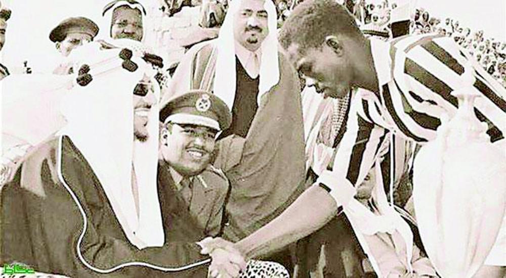 الملك سعود يصافح أحد لاعبي الاتحاد ويهنئه بالفوز على منتخب الرياض. (أرشيف عكاظ)