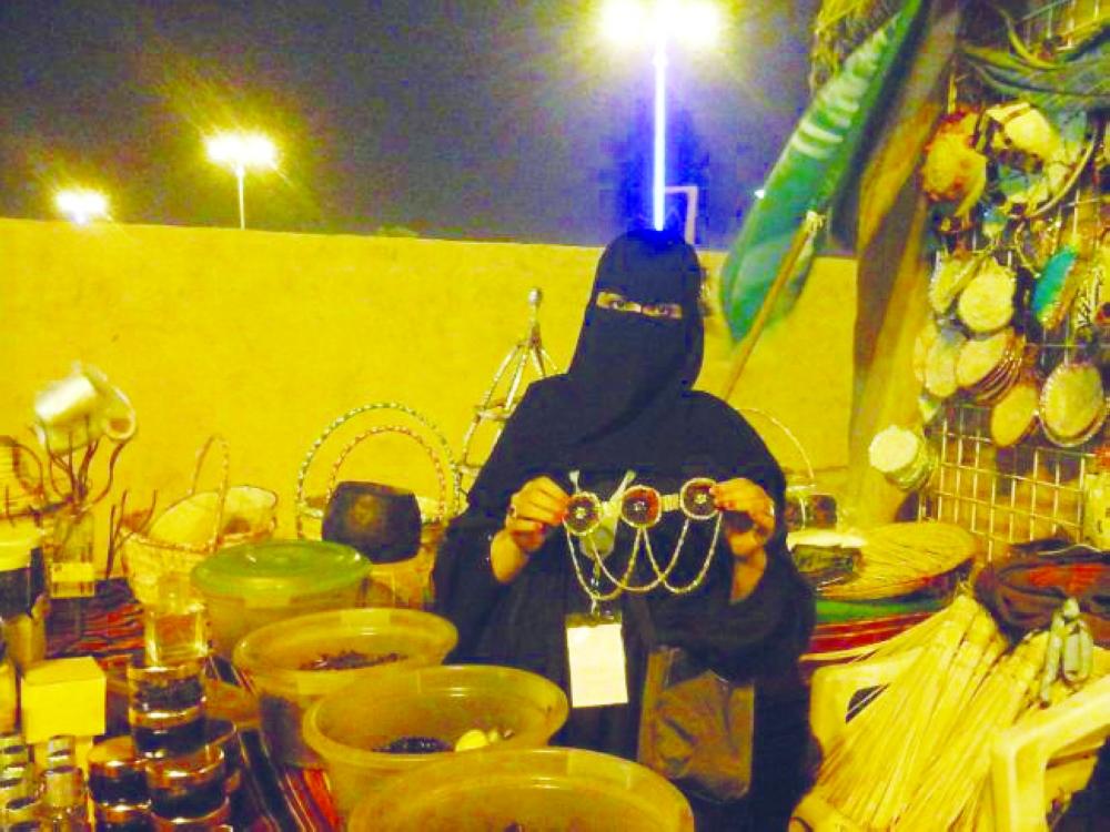فتاة تعرض مشغولات يدوية في إحدى الأسواق التراثية بجازان. (عكاظ)
