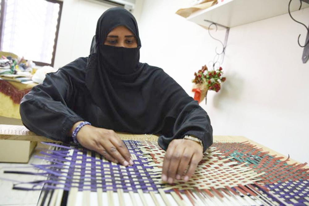 سيدة تعمل على تجهيز سعف النخل لإنتاج الحقائب النسائية في الجمعية الفيصلية في جدة. (تصوير: أمل السريحي)