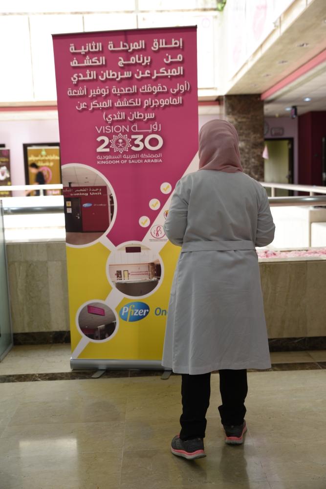 سيدة من الكادر التمريضي تطالع إعلان الفحص المبكر لسرطان الثدي ضمن حملة التوعية في شهر إكتوبر