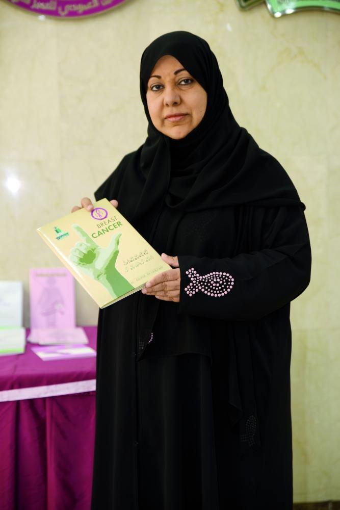 سامية العمودي تشير إلى كتاب «حقوق المريضات عبر التمكين الصحي». (تصوير: أمل السريحي)