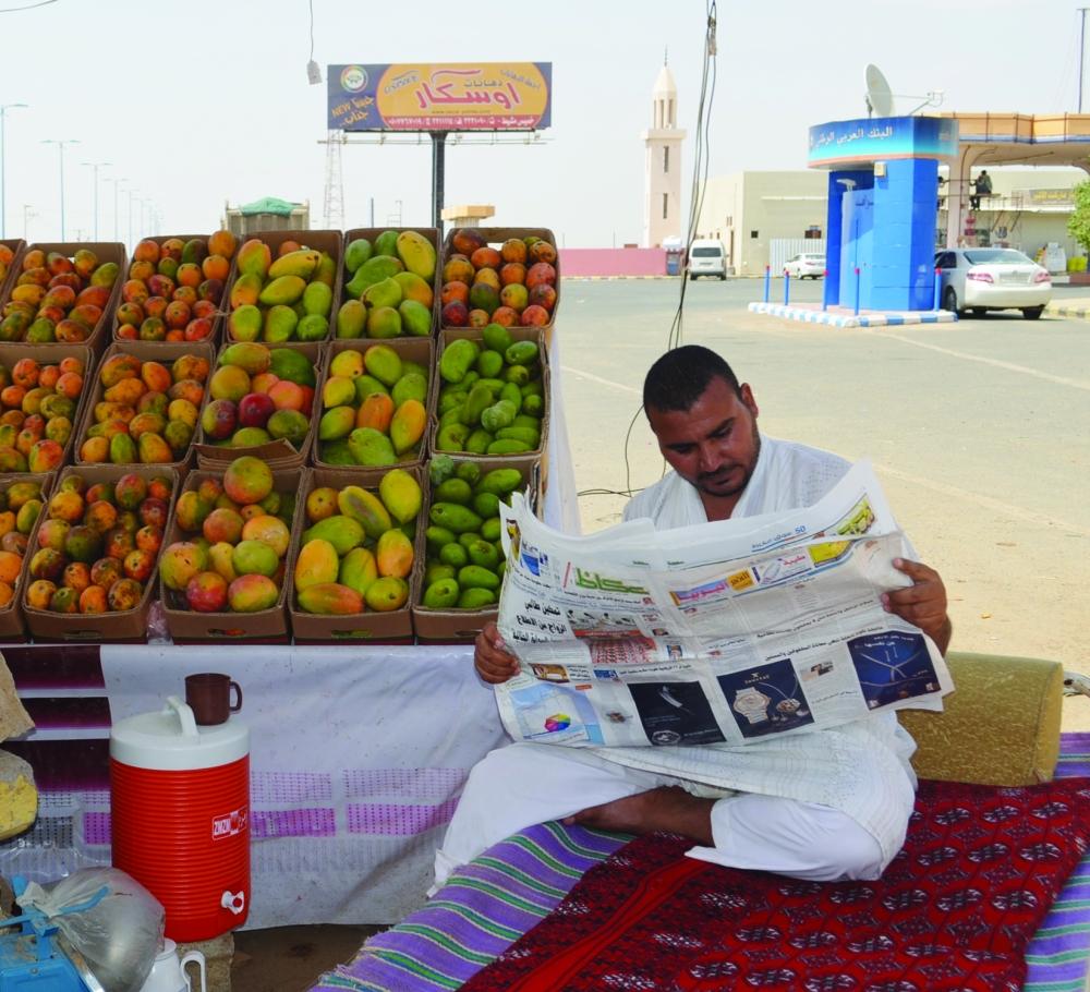 بائع الفواكه محمد عبدالحليم متصفحا «عكاظ».