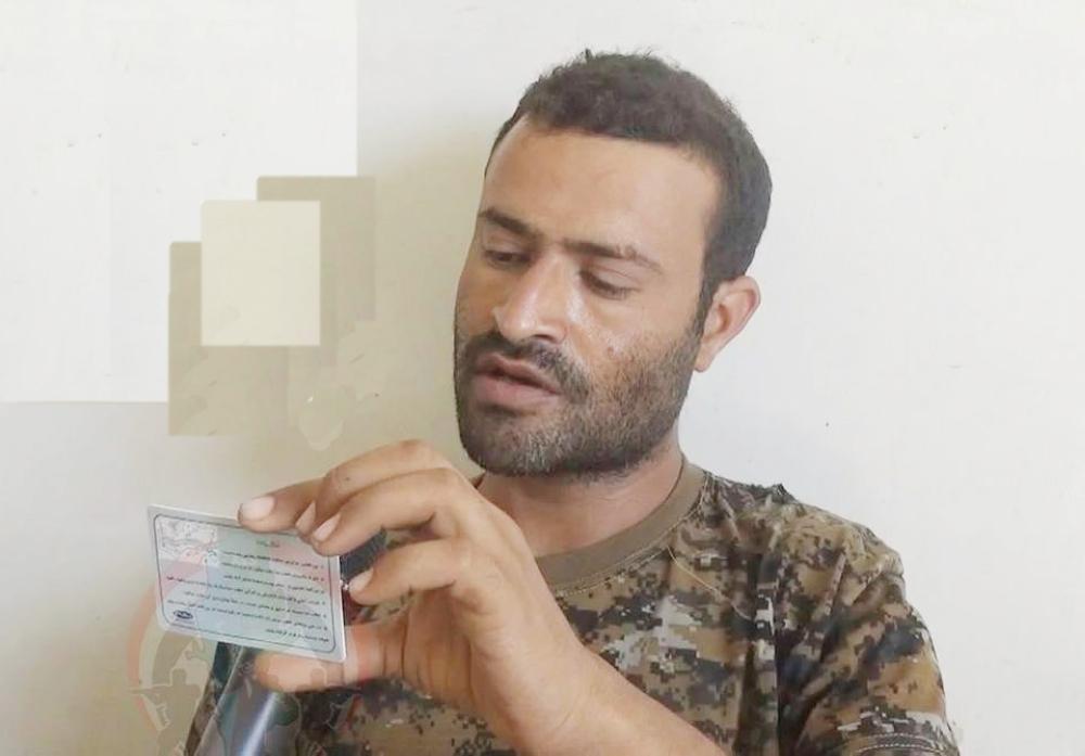 القيادي الحوثي وبيده بطاقته الإيرانية.  (عكاظ)