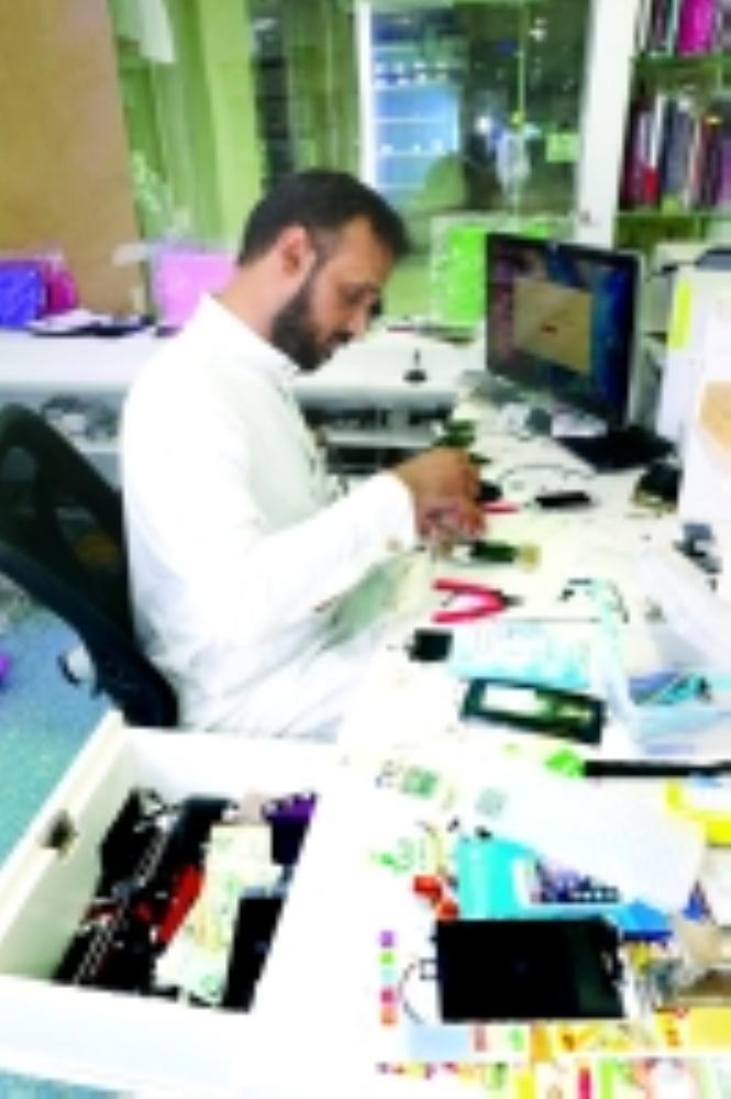 شاب سعودي يقوم بصيانة أحد الجوالات.  (تصوير: أحمد المقدام)