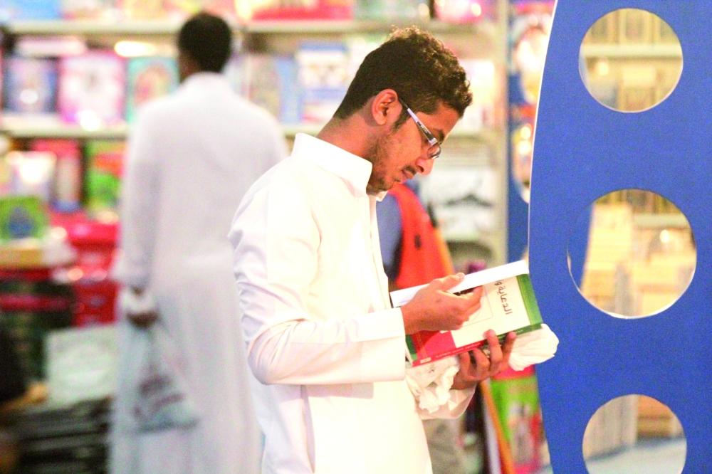 شاب يتصفح كتابا في أحد معارض الكتاب. (تصوير: فيصل مجرشي)