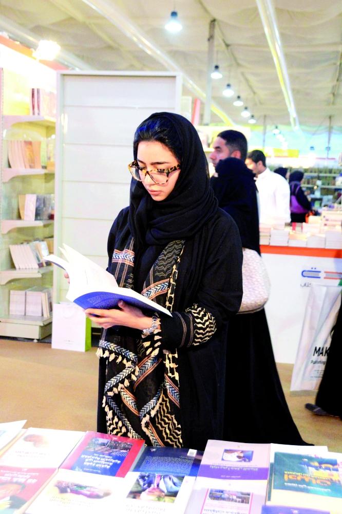 فتاة تتصفح كتابا في إحدى دور النشر المشاركة في معرض الكتاب الذي أقيم في جدة أخيرا.  (تصوير: ناصر محسن)