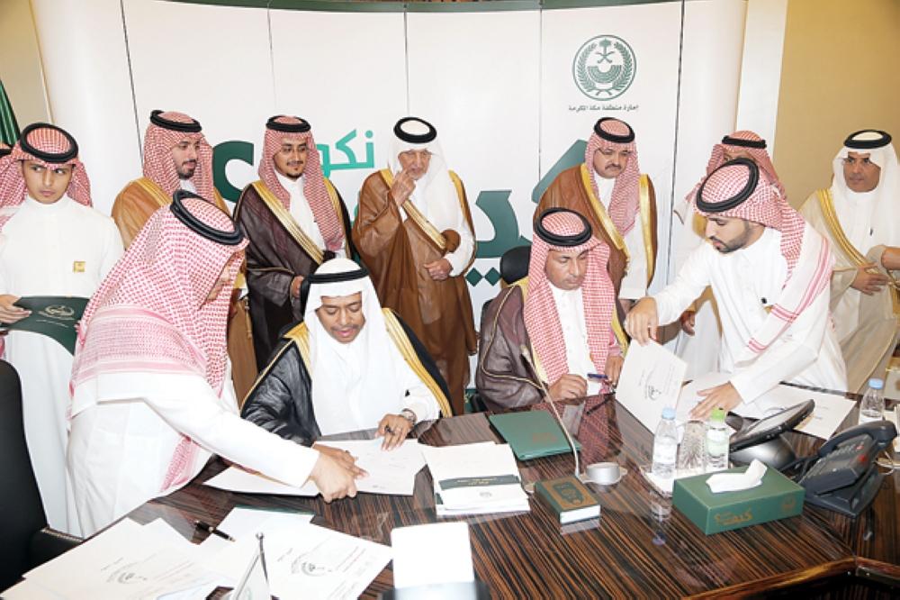الأمير خالد الفيصل يشهد توقيع الاتفاقات. (عكاظ)