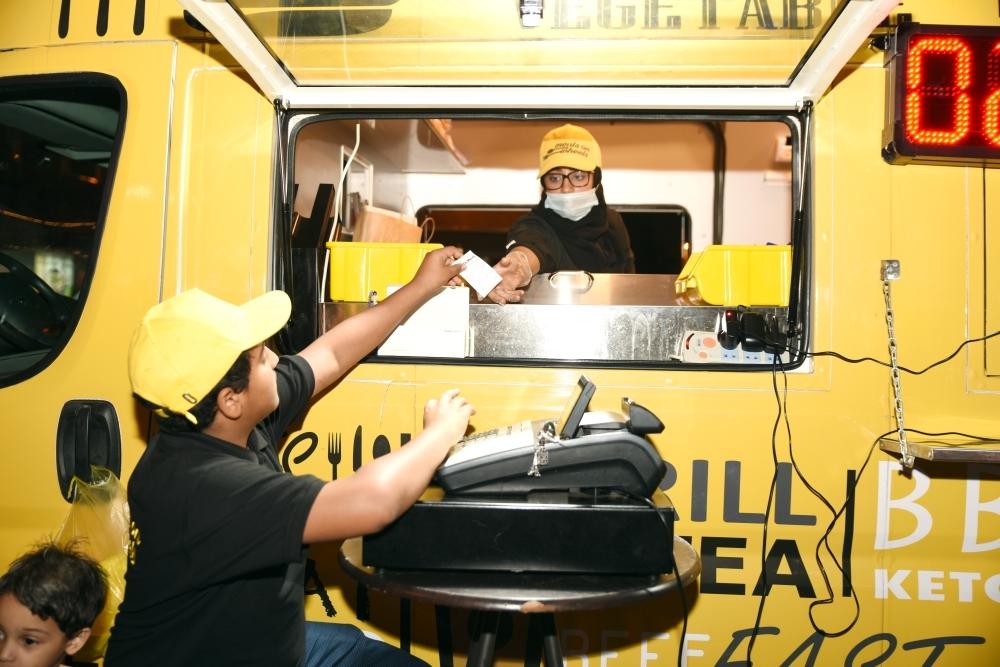 فتيات يعملن في سيارة للوجبات السريعة.