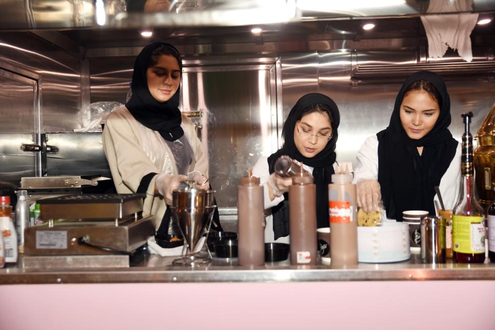 سعوديات يجهزن «الكوكيز» للزبائن.