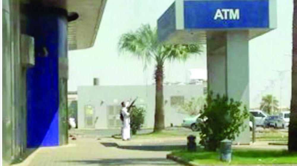 صورة متداولة للمتهم حاملاً الرشاش أثناء اقتحامه للمصرف.