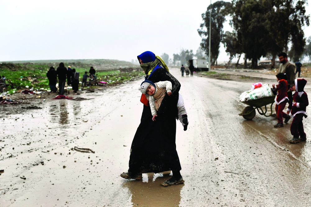 عراقية نازحة مع طفلها خارج الموصل أمس.  (أ. ف. ب)
