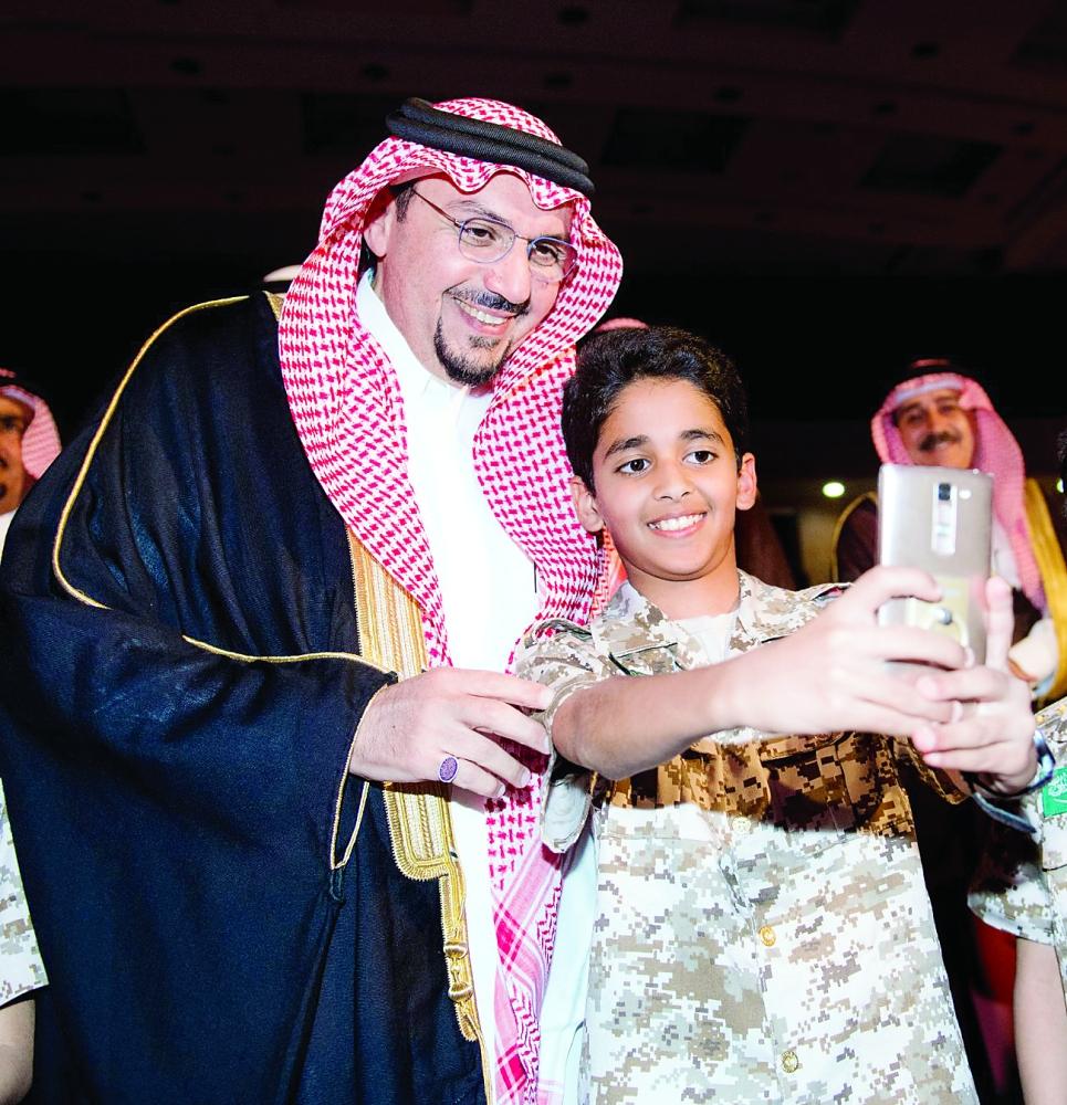 أحد المكرمين يلتقط صورة سيلفي مع أمير القصيم. (عكاظ)