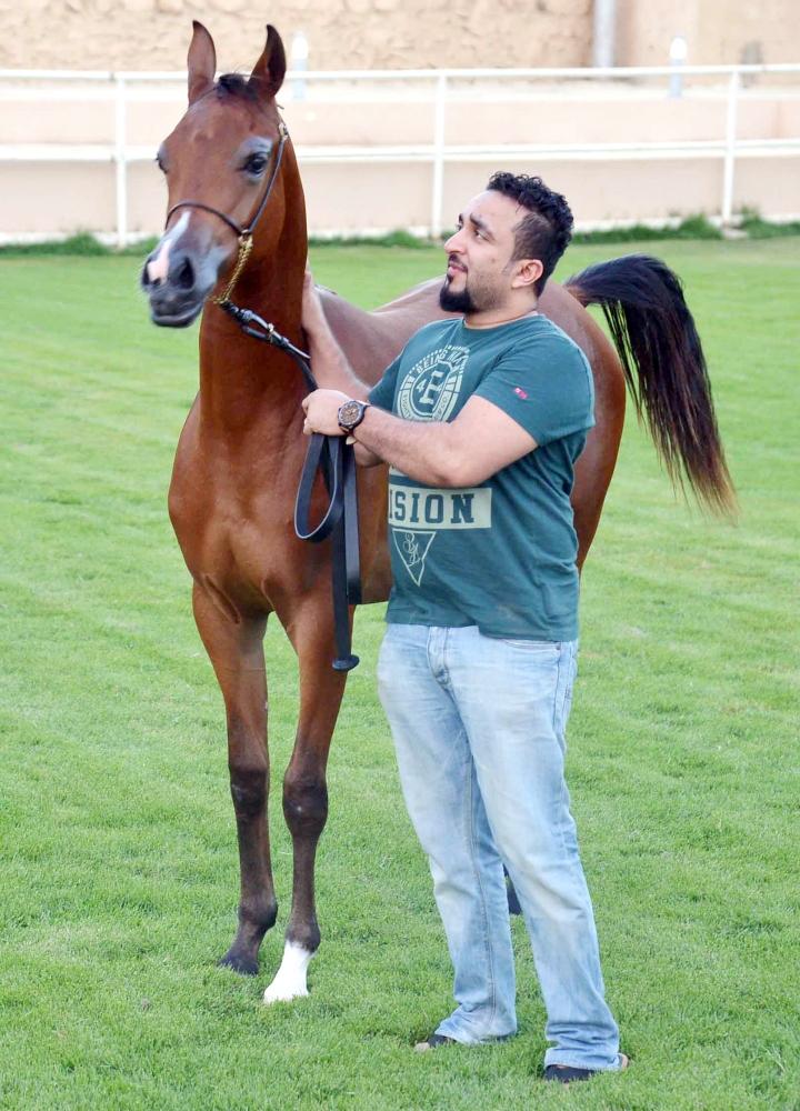 عبدالله يروض أحد الخيول الخاصة بمربطه في جدة.  (عكاظ)