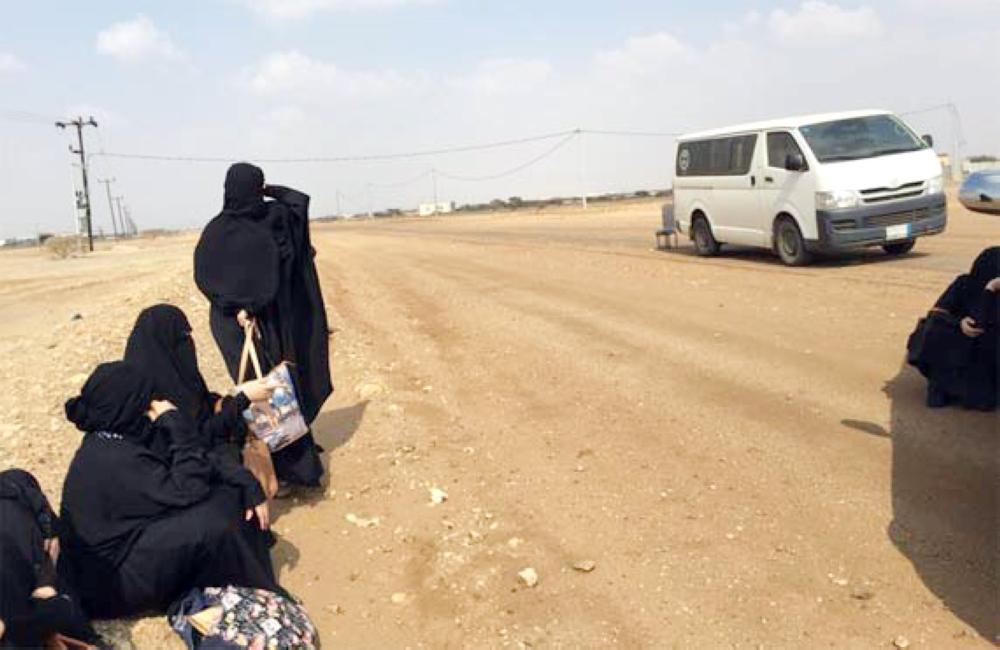 معلمات ينتظرن سيارة تقلهن بعد انتهاء اليوم الدراسي في إحدى مناطق جازان. (عكاظ)