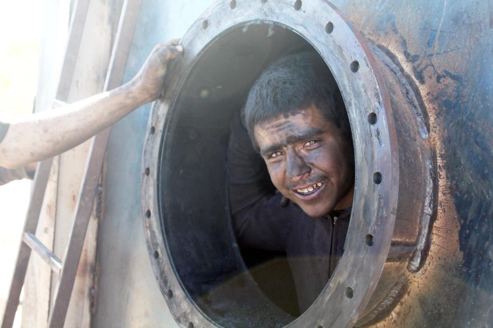 أحد العاملين من داخل محرقة لتكرير النفط. (عكاظ)