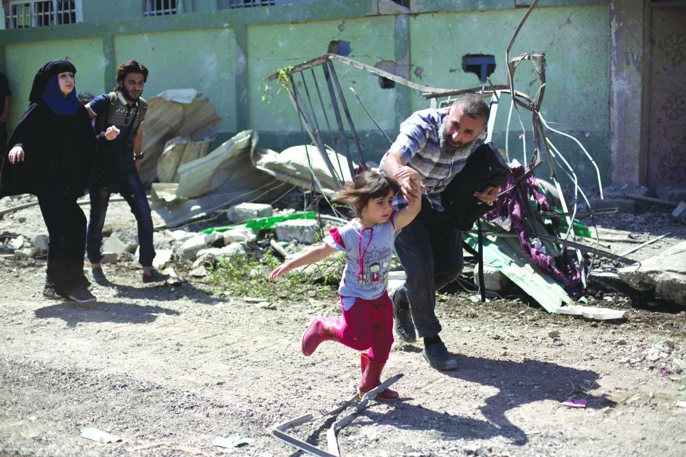 عراقيون يفرون من المعارك الدائرة غرب الموصل بين «داعش» والجيش العراقي أمس الأول. (أ. ف. ب)