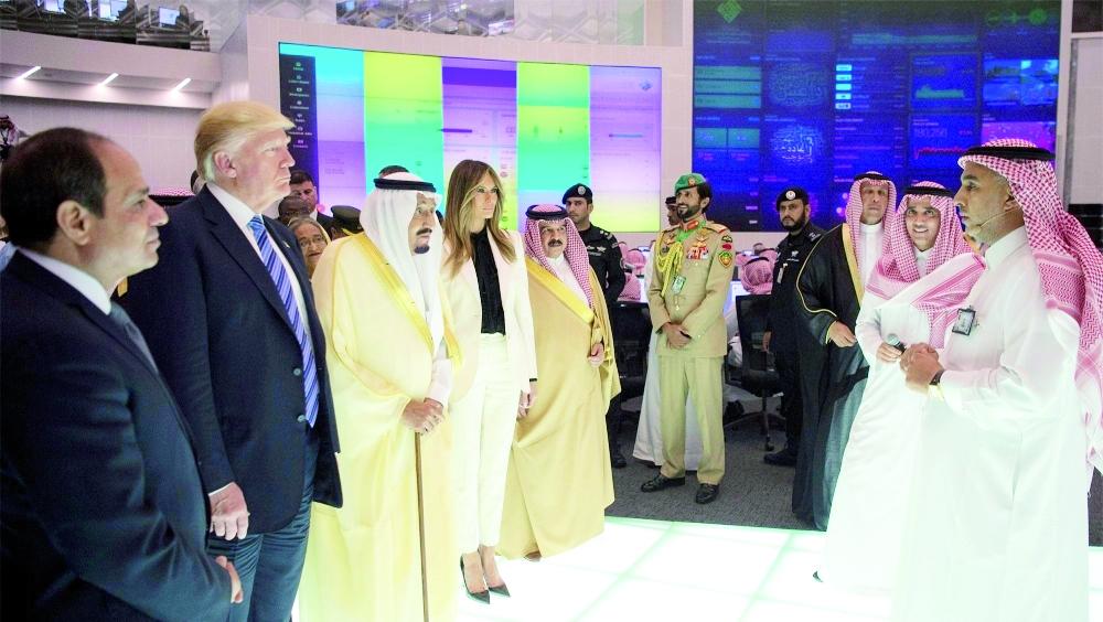 الملك سلمان وترمب وزوجته وعدد من القادة يستمعون إلى شرح عن مركز الاعتدال.