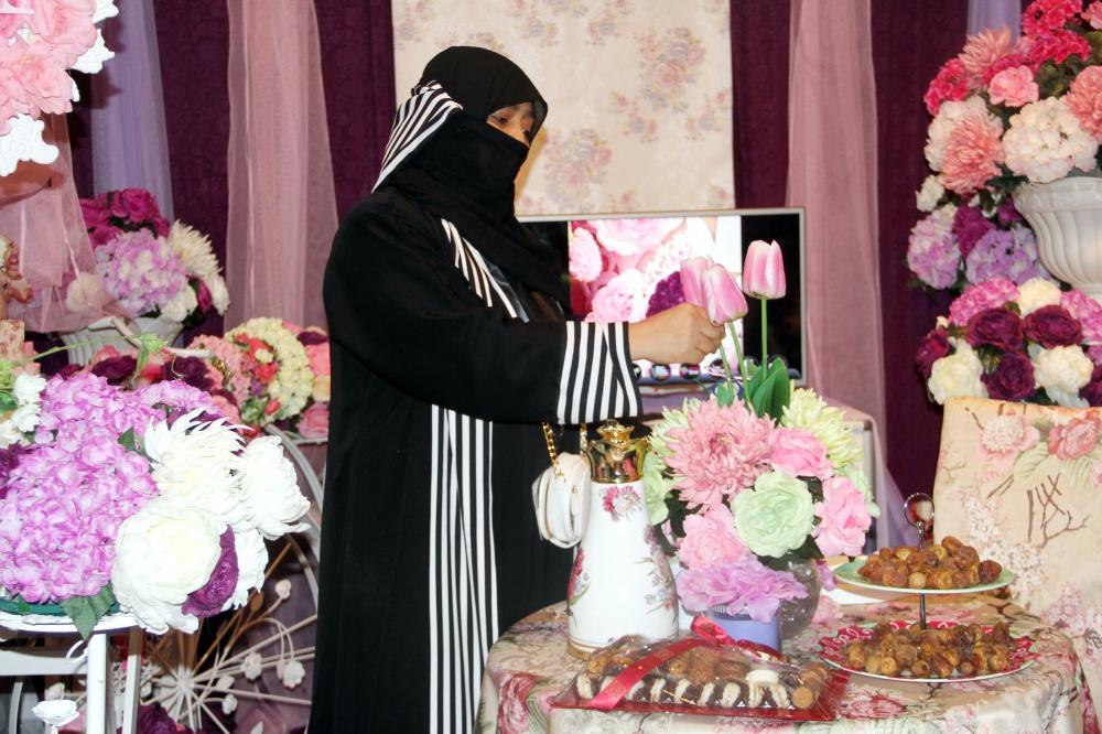 سيدة تنسق الزهور في أحد المعارض النسائية. (تصوير: أمل السريحي)