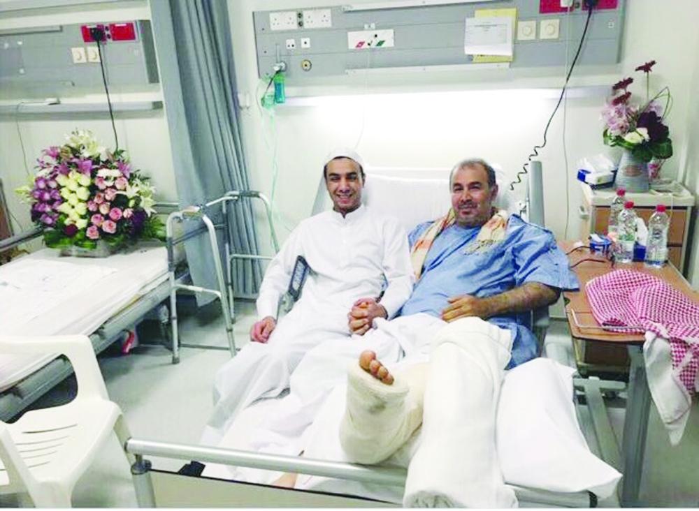 علي النمر مع والده في المستشفى.  (عكاظ)