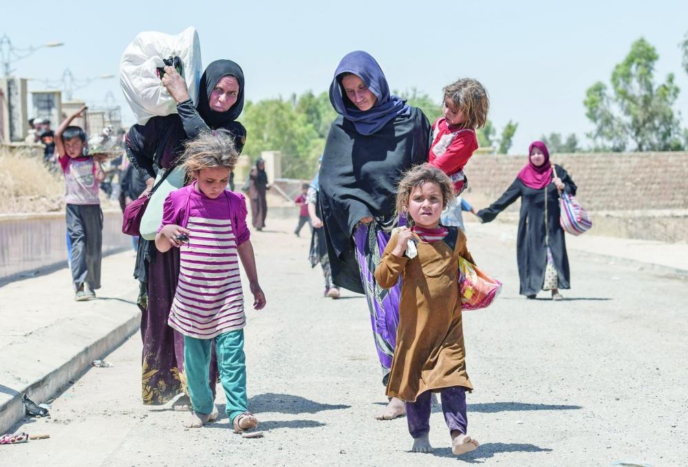 عراقيات نازحات من الموصل إلى معسكر مؤقت في مجمع فندق نينوى الدولي المغلق  أمس الأول. (أ. ف. ب)