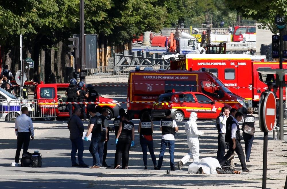 شرطة مينال تفتش جثة مشتبه به في مكان الحادث (رويترز)