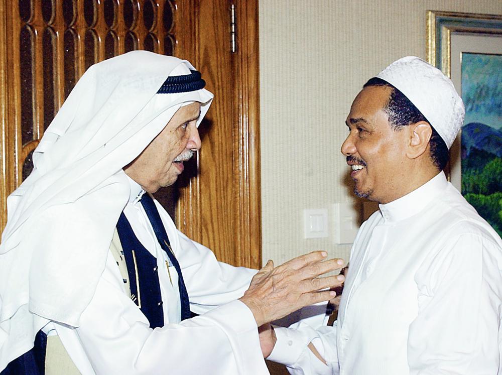 الراحل في مناسبة اجتماعية مع محمد عبده. (أرشيف «عكاظ»)