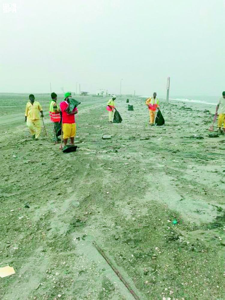 مشاركون في حملة تنظيف الشاطئ. (عكاظ)