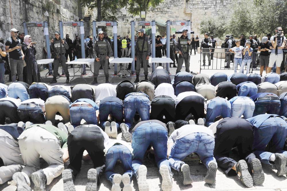 فلسطينيون يؤدون صلاة الظهر خارج المسجد الأقصى أمس. (أ. ف. ب)