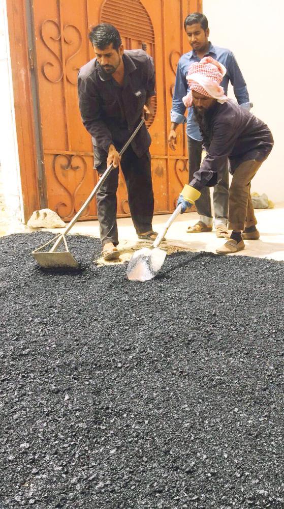 عمال بلدية بيشة خلال إصلاحهم الطريق أمام المنزل.