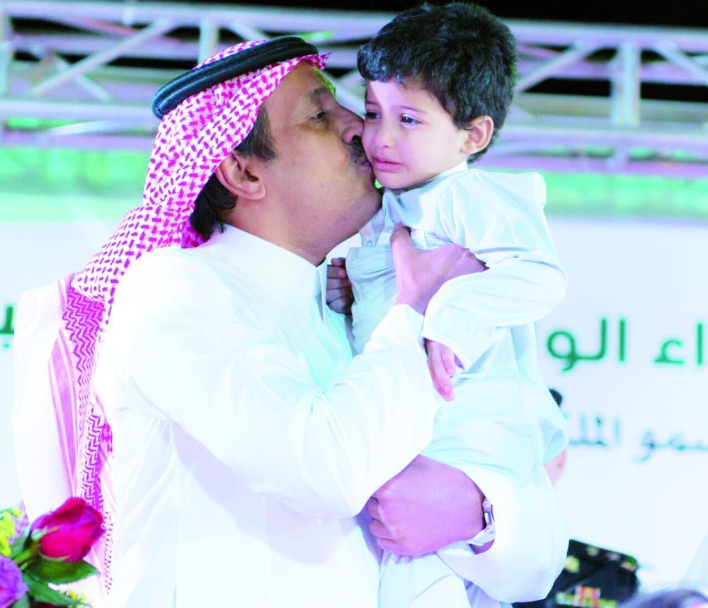 أمير الباحة يطبع قبلة على أحد أبناء شهداء الوطن. (عكاظ)