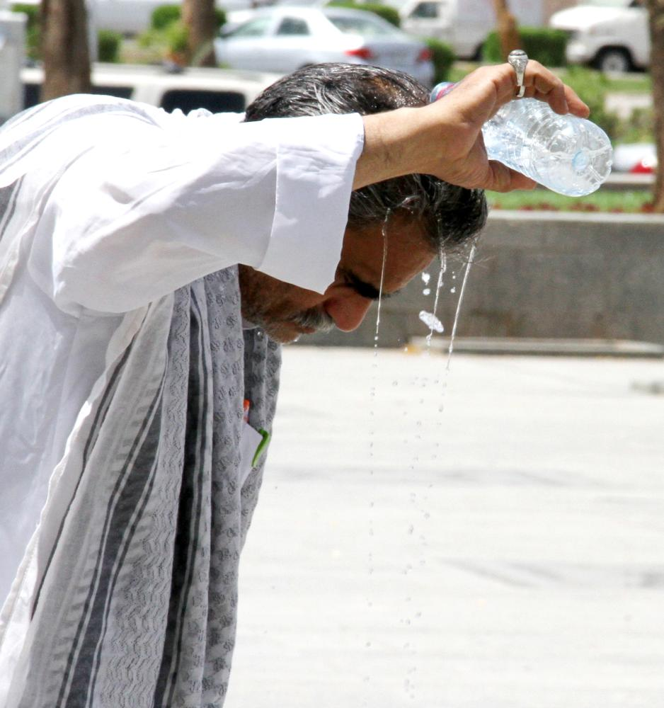 حاج يبلل رأسه بقارورة ماء بارد للتخفيف من درجة الحرارة التي وصلت 45 درجة مئوية بالمدينة المنورة