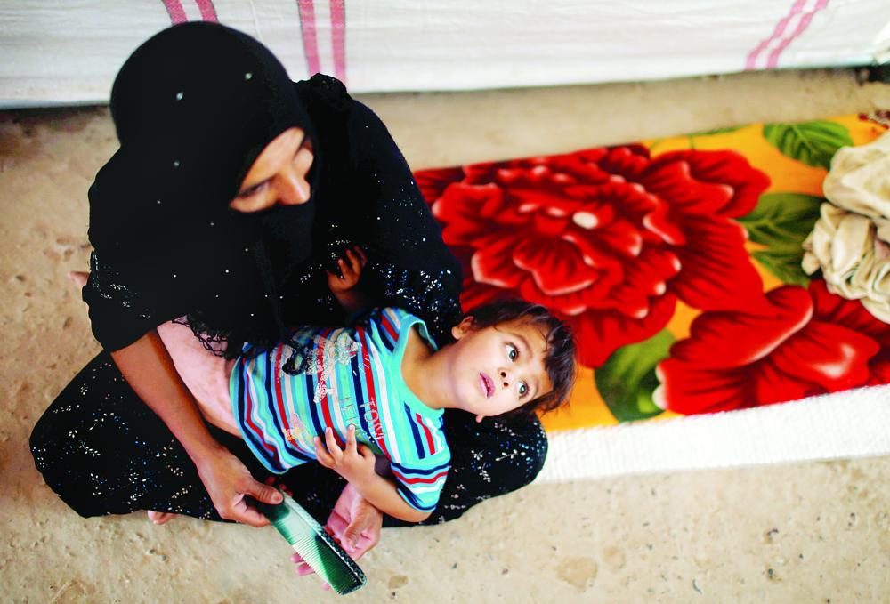 نازحة عراقية تحمل طفلتها داخل خيمة في مخيم للنازحين جنوب الموصل أمس. (رويترز)