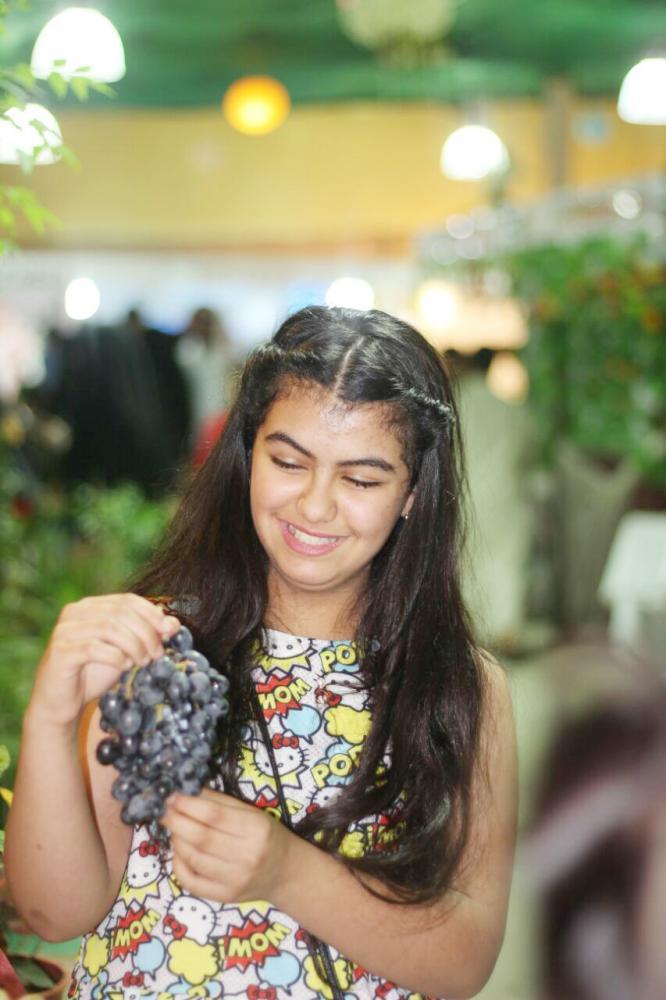 طفلة تمسك عنقودا من العنب في مهرجان الورد والفاكهة بتبوك. (عكاظ)