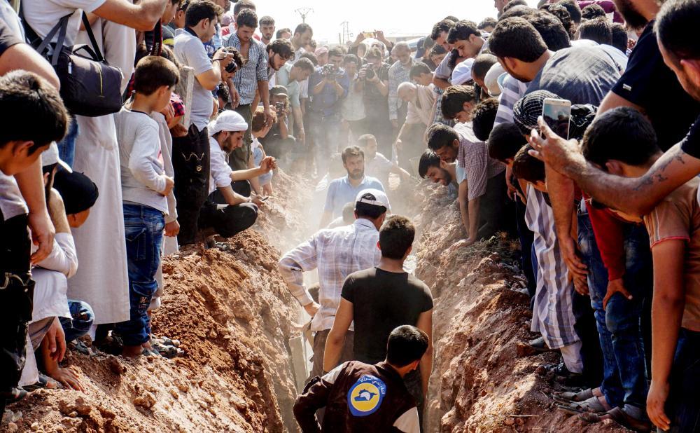 سوريون خلال عملية دفن قتلى الخوذ البيضاء في سرمين. (أ. ف. ب)