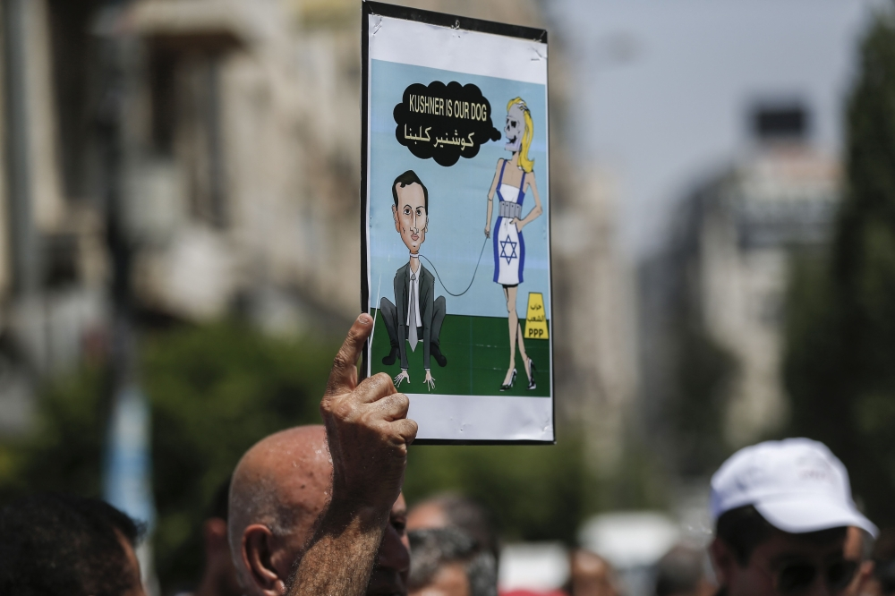 A picture taken on August 24, 2017 in the West Bank city of Ramallah shows a Palestinian demonstrator holding a cartoon depicting Senior White House Advisor Jared Kushner, during a protest against the arrival of a US delegation headed by Kushner to meet with Palestinian president Mahmoud Abbas. / AFP / ABBAS MOMANI