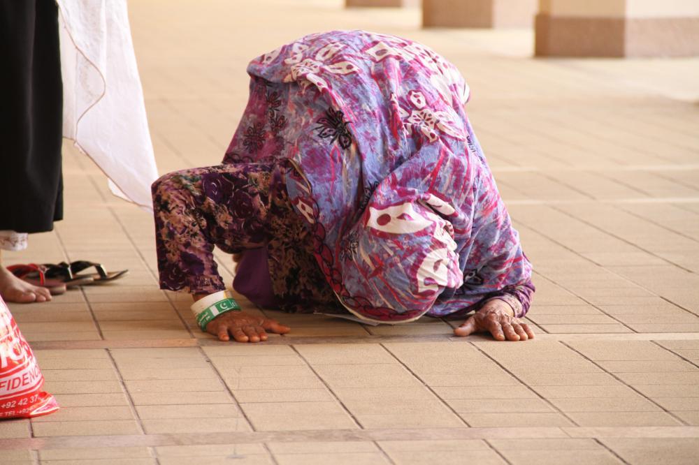 حاجة تسجد لله شكرا لمغادرتها إلى المشاعر المقدسة ظهر أمس. ( تصوير: عبدالمجيد الدويني @ocxco)