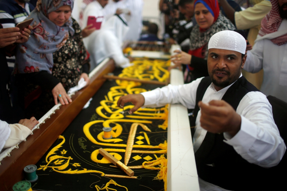 A man embroiders the Kiswa, a silk cloth covering the Holy Kaaba, ahead of the annual Haj pilgrimage, at a factory in the holy city of Makkah on Sunday. — Reuters