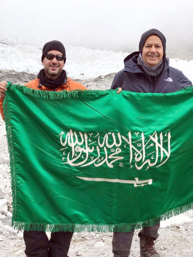 عضو الشورى السعدون وابنه يحملان العلم السعودي من أعلى قمة إيفرست. (عكاظ)