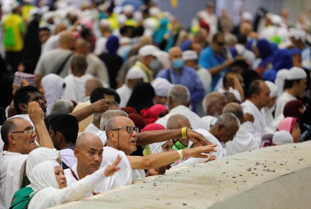 Muslim pilgrims cast stones at a pillar that symbolises Satan during the annual haj pilgrimage in Mena, Saudi Arabia September 1, 2017.  REUTERS/Suhaib Salem