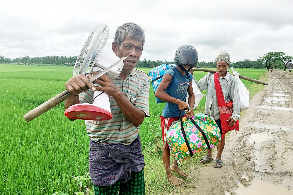 أسرة روهينجية مشردة متجهة إلى بنغلاديش. (أ.ف.ب)