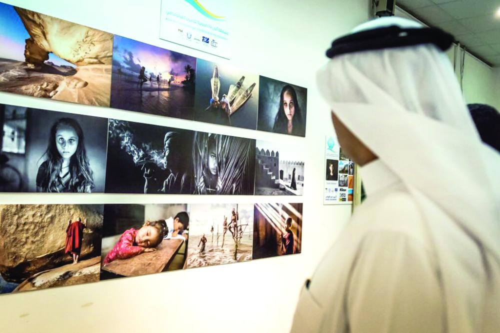 زائر يتابع صوراً فائزة بالمسابقة عرضت في المعرض المصاحب. (عكاظ)