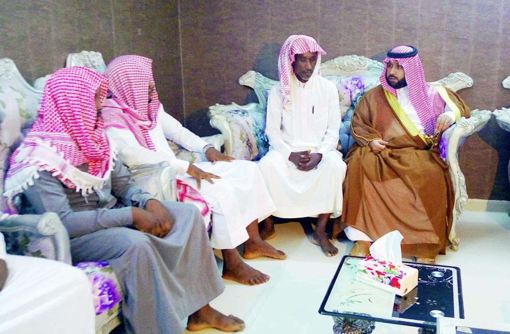 الأمير محمد بن عبدالعزيز معزيا أسرة الشهيد. (عكاظ)