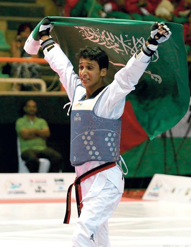 البطل محمد السويق يحمل علم المملكة بعد تتويجه بالذهب.