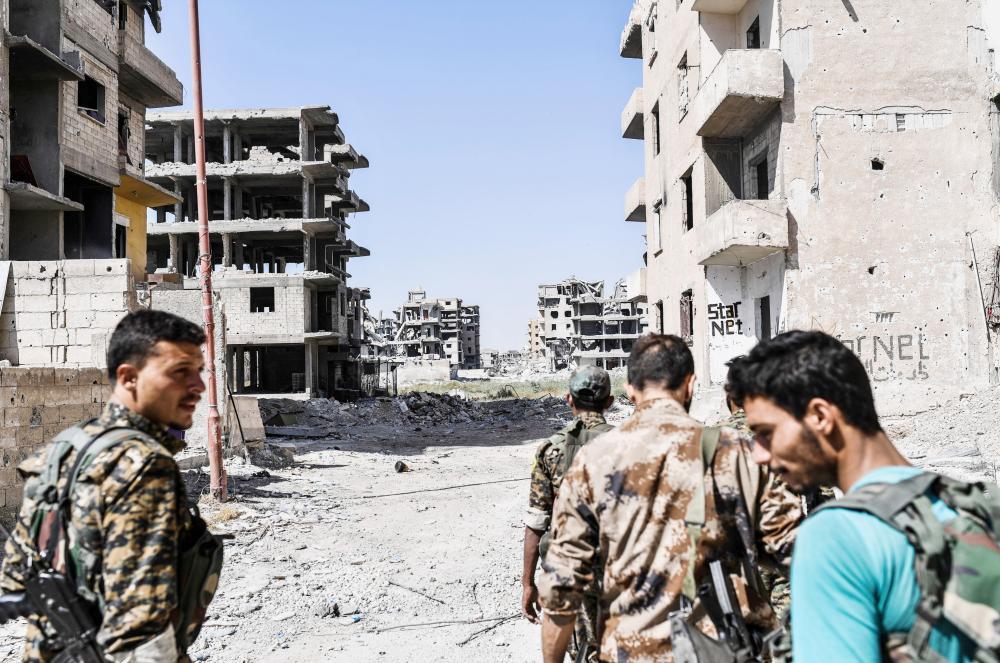 مقاتلون من «سورية الديمقراطية» في أحد شوارع الرقة أمس الأول. (أ ف ب)