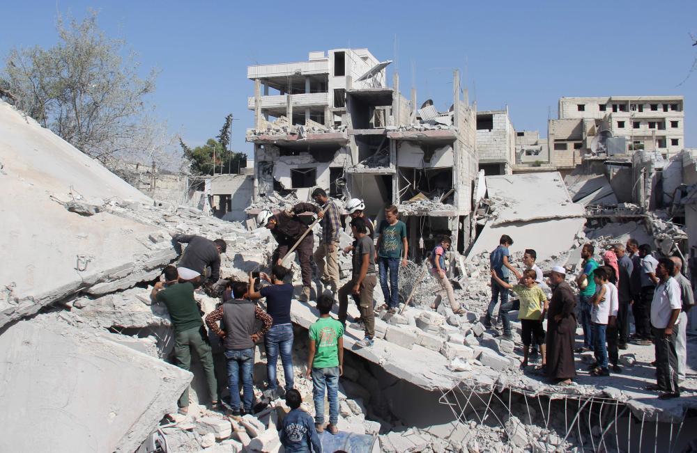 سوريون يبحثون عن الضحايا وسط أنقاض مبنى بعد غارة على مدينة حريم شمال غرب إدلب أمس الأول. (أ.ف.ب)