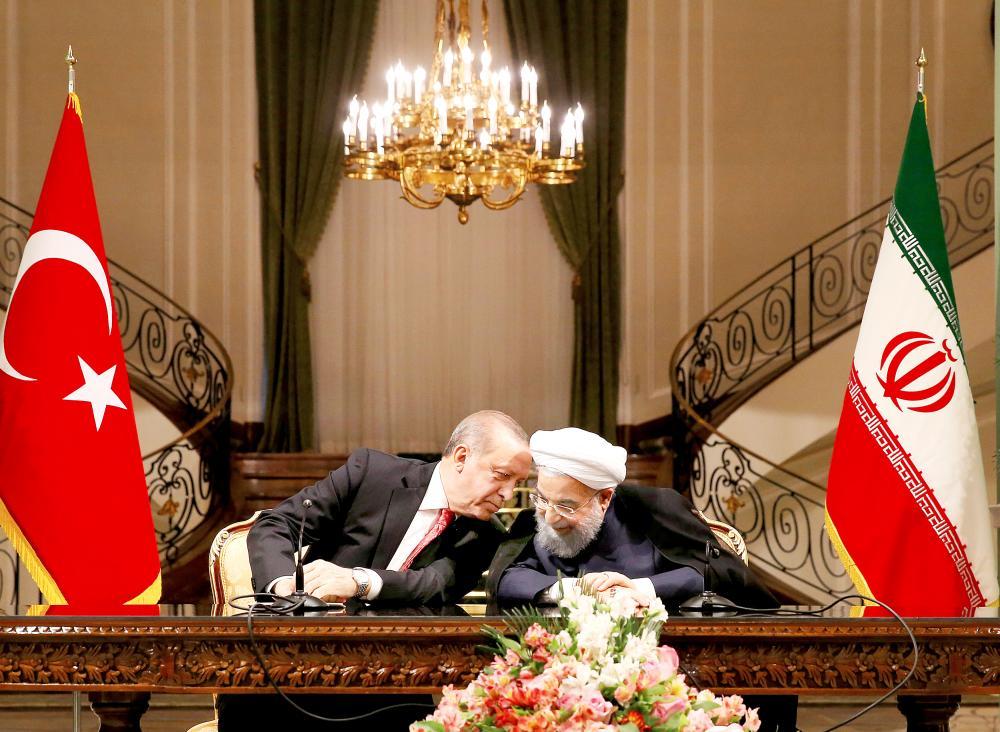 أردوغان يهمس في أذن روحاني خلال مؤتمرهما الصحفي في طهران أمس. (أ.ب)