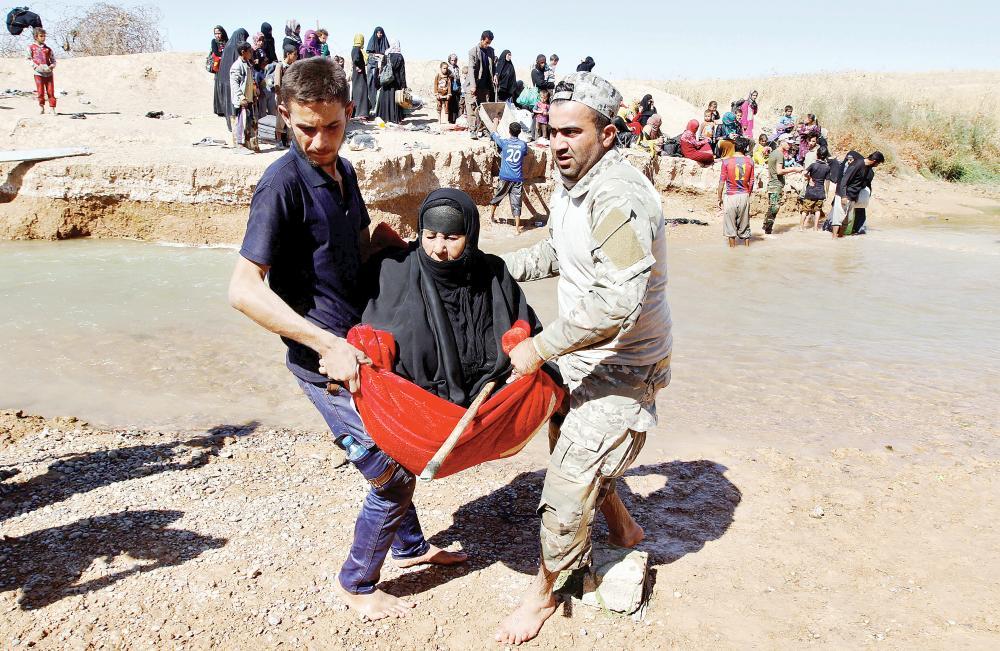 عراقيان يحملان لاجئة فرت من الحويجة أمس. (رويترز)