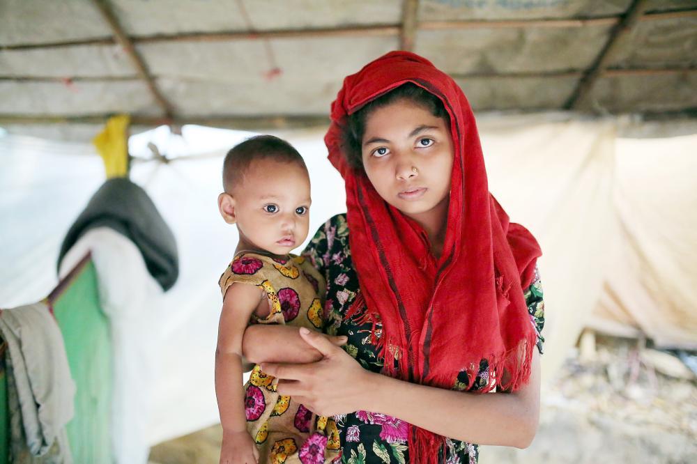 روهينغية تحمل طفلها في مخيم للاجئين في بنغلاديش عقب فرارها من بورما أمس الأول. (أ. ف. ب)