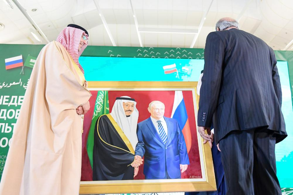 وزيرا ثقافة البلدين أمام لوحة للملك سلمان وبوتين عقب افتتاح الأسبوع الثقافي السعودي أمس. (واس)